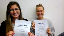 Digitaler Abschlussworkshop: Marleen und Claudia halten ihre Zertifikate in die Kamera.