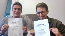 Digitaler Abschlussworkshop: Marek und Roch halten ihre Zertifikate in die Kamera.